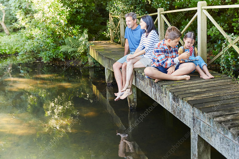Family relaxing on footbridge over pond