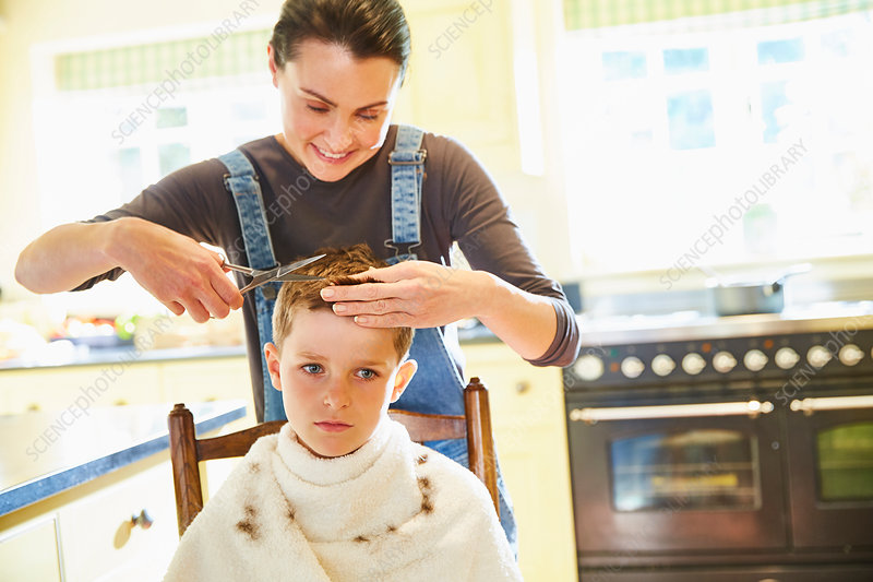 Unhappy boy getting haircut from mother
