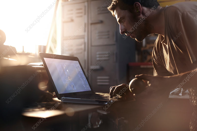 Blacksmith using laptop in forge