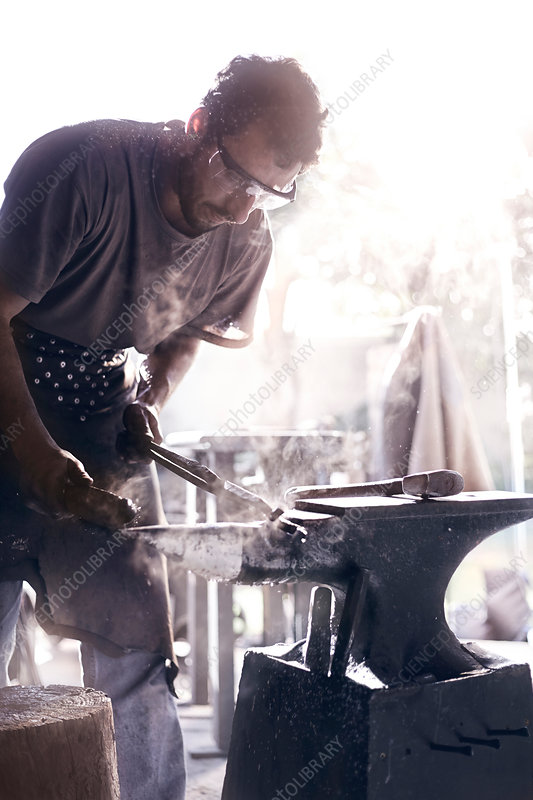 Blacksmith shaping iron over anvil