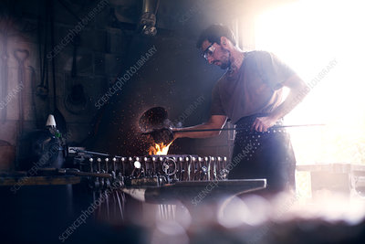 Blacksmith working at fire in forge