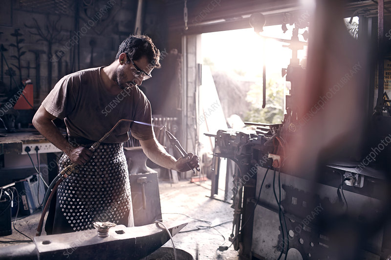 Blacksmith using blow torch in forge