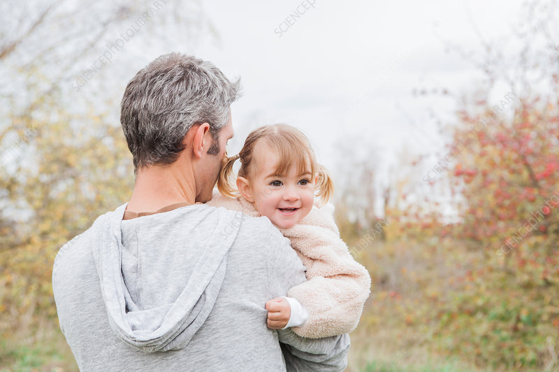 Father holding smiling toddler girl