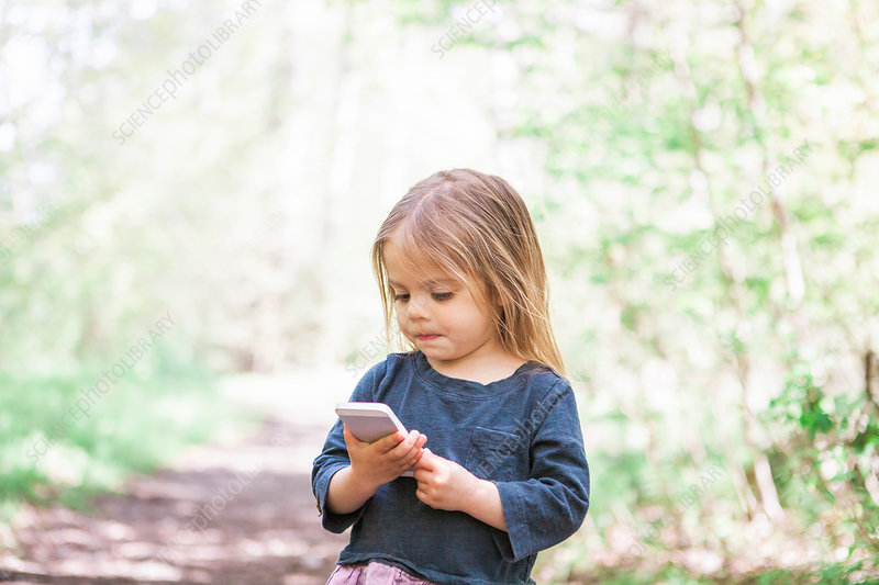 Toddler girl using cell phone in park