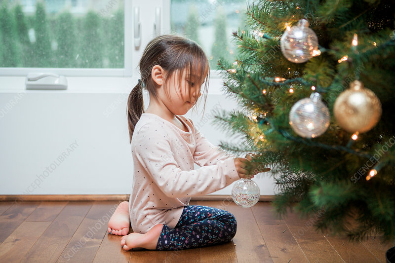 Toddler girl decorating Christmas tree