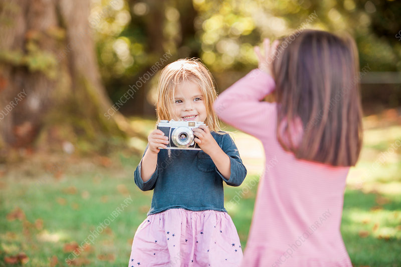 Toddler girls playing with camera in park
