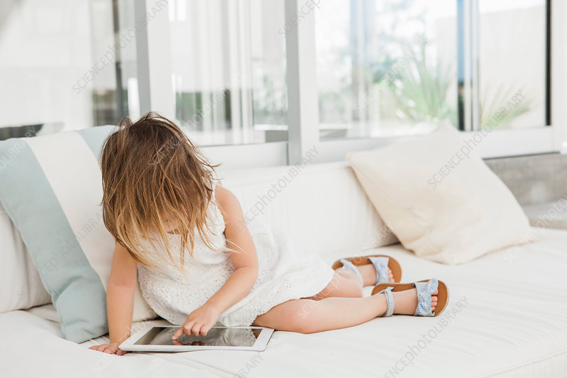 Toddler girl using digital tablet on sofa