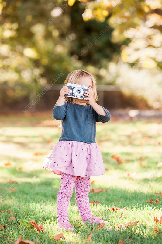Toddler girl using retro camera in park