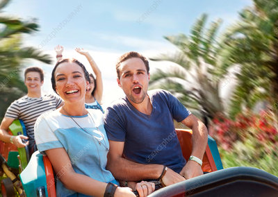 Couple cheering on amusement park ride