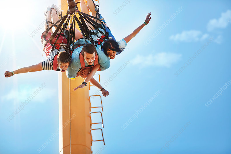Friends bungee jumping at amusement park