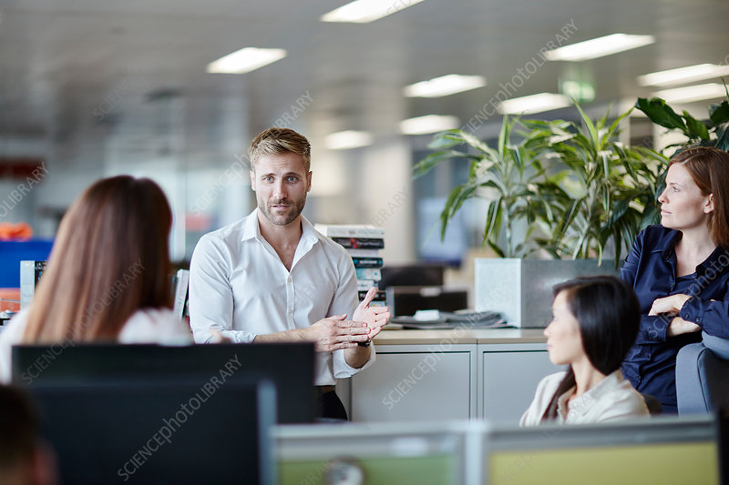 Businessman leading meeting cubicle