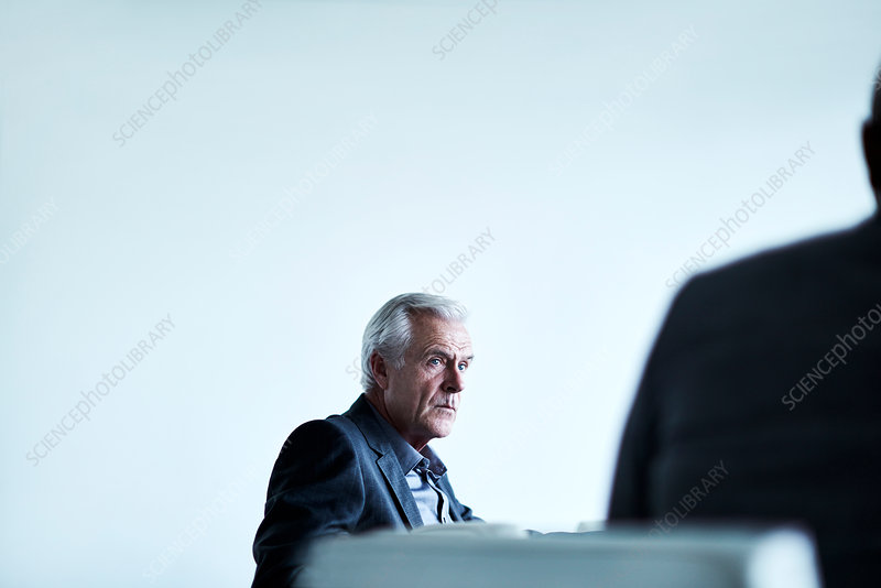 Serious senior businessman listening