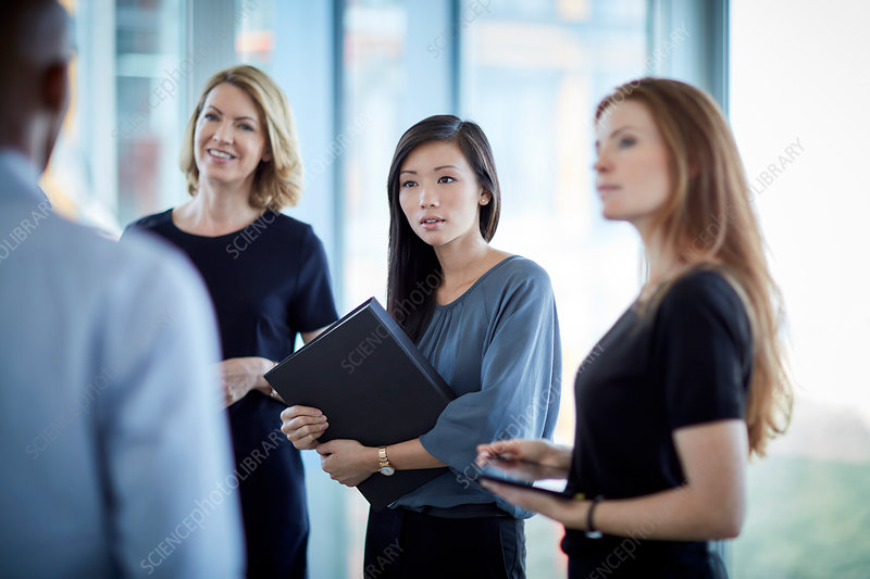 Businesswomen listening to businessman