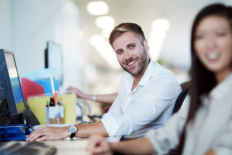 Smiling businessman at computer in office