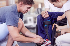 Physical therapist tying man's shoe