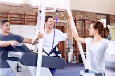 Man high fiving physical therapist