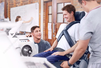 Physiotherapists guiding man at machinery