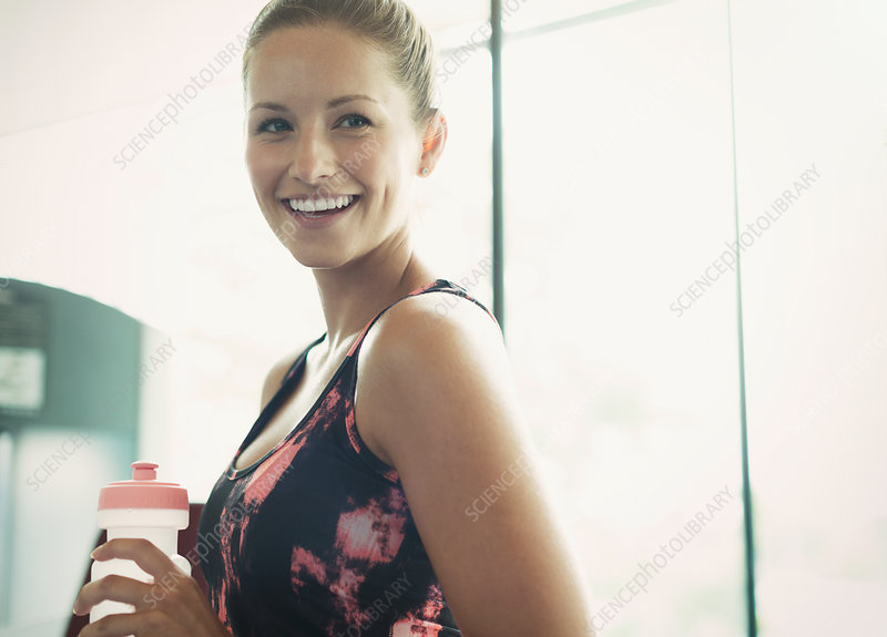 Woman with water bottle at gym