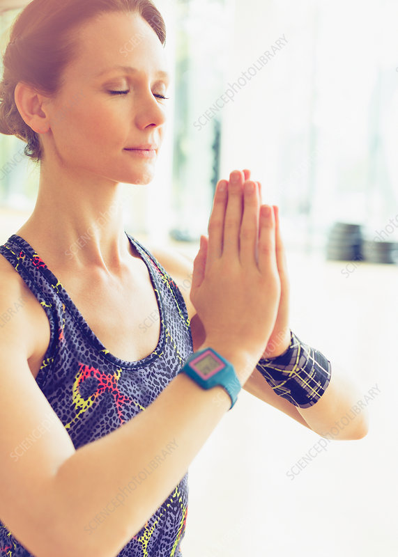 Woman practicing yoga with hands clasped