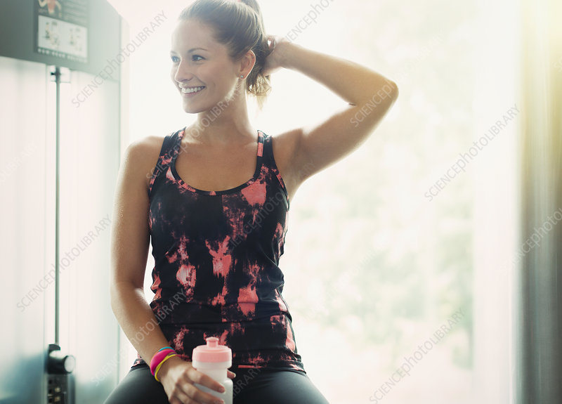 Woman with water bottle resting at gym