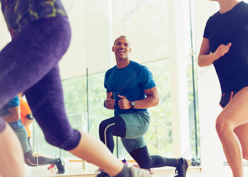 Smiling man lunging in exercise class