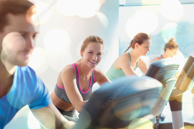 Smiling woman riding exercise bike at gym