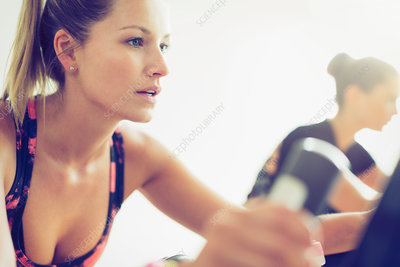 Focused woman riding exercise bike