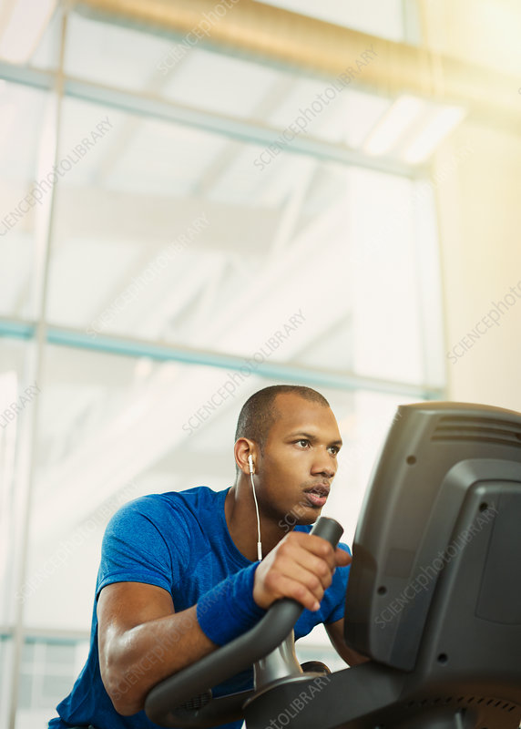 Determined man on elliptical trainer