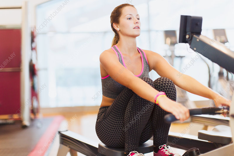 Woman using rowing machine at gym