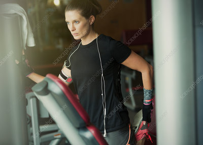 Focused woman stretching leg at gym