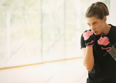 Focused woman shadow boxing in gym studio
