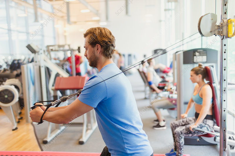 Man using cable exercise equipment at gym