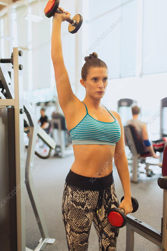 Focused woman lifting dumbbell overhead