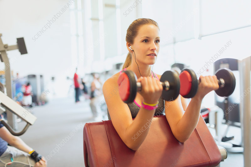 Woman doing dumbbell biceps curls at gym