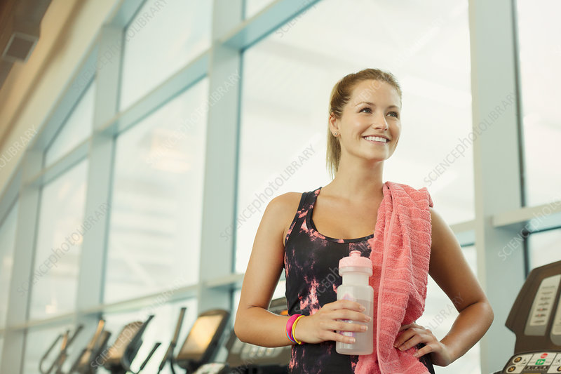 Woman resting and drinking water at gym