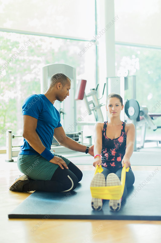 Personal trainer guiding woman