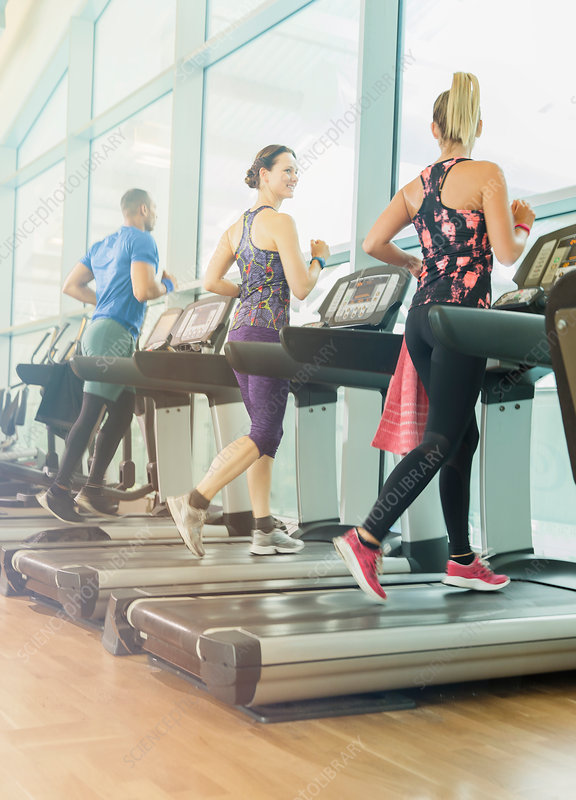 Man and women jogging on treadmills