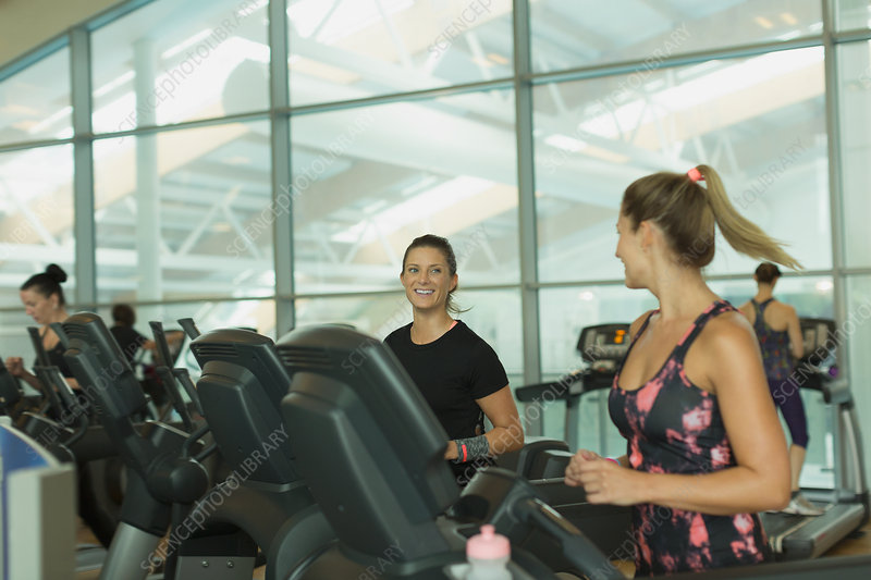 Women talking and jogging on treadmills
