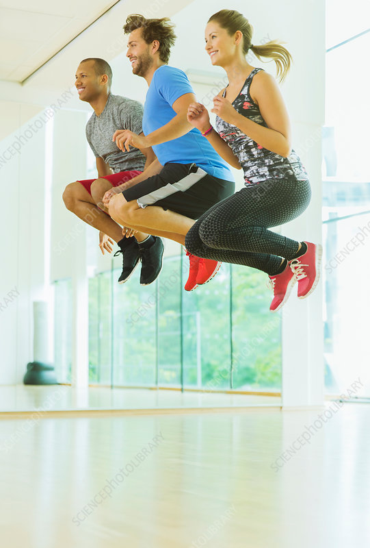 Men and woman jumping in exercise class