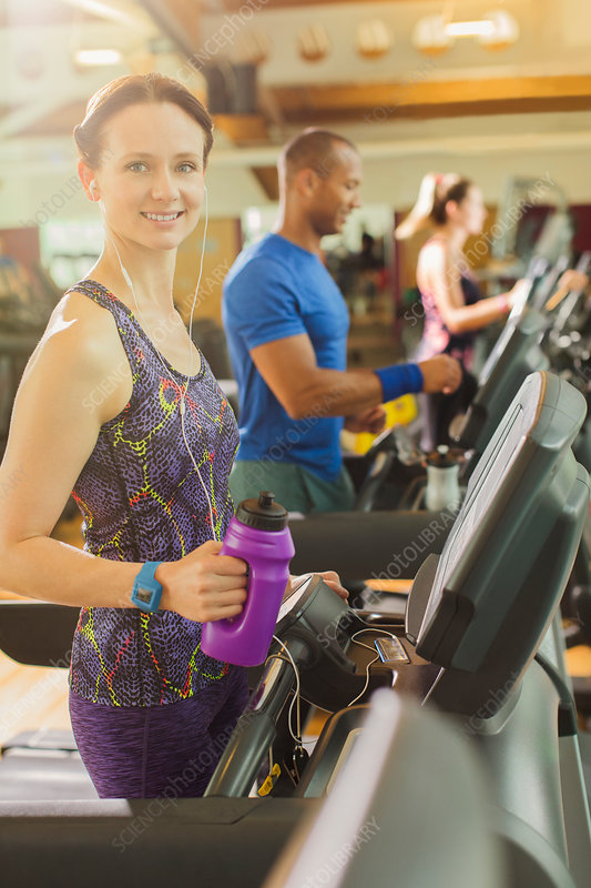 Woman with water bottle on treadmill