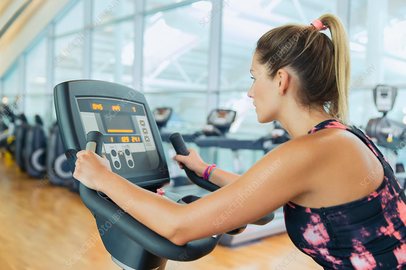 Woman riding exercise bike at gym