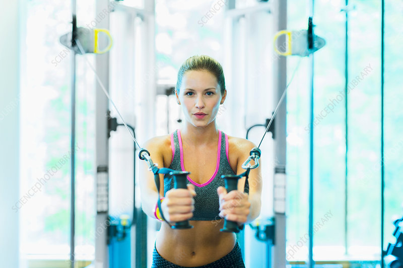 Woman using cable exercise equipment