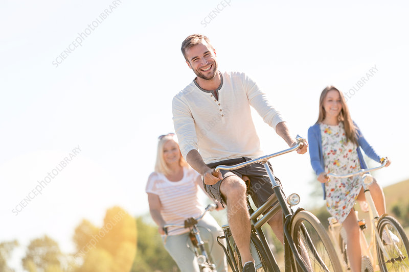 Smiling young man bike riding with women