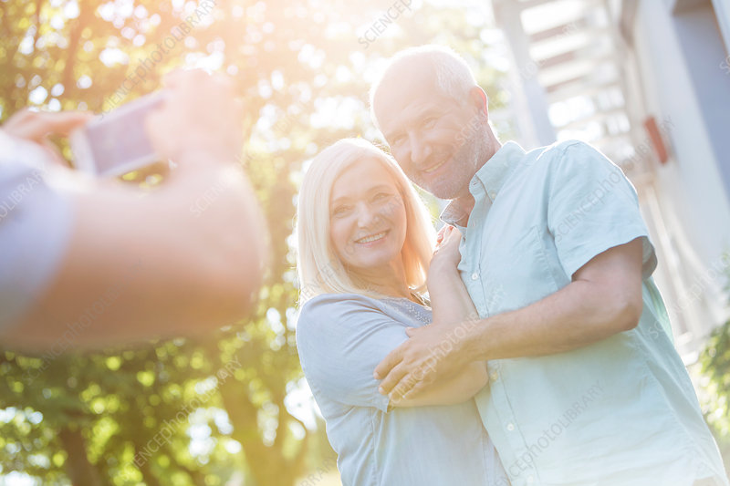 Man photographing senior couple outdoors