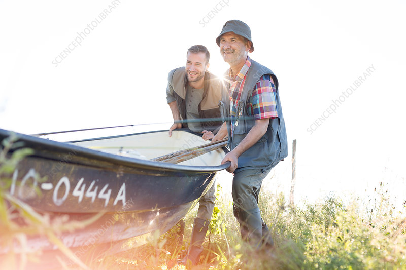 Father and adult son lifting fishing boat