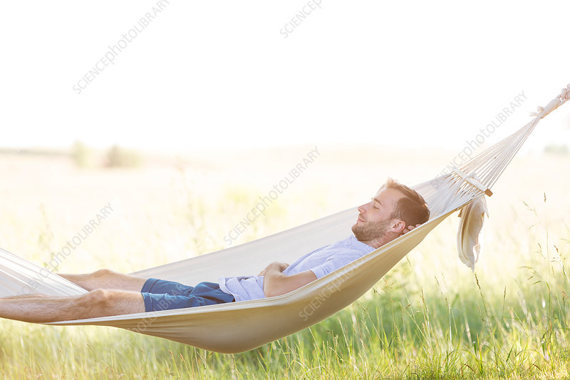 Young man sleeping in summer hammock