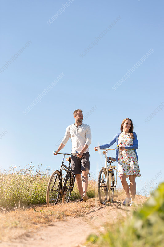 Couple walking bicycles on dirt road