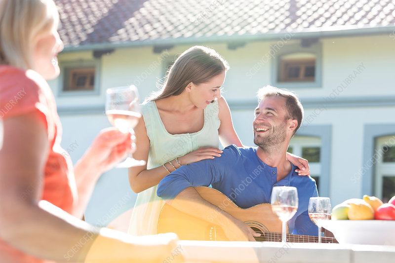 Couple playing guitar and drinking wine