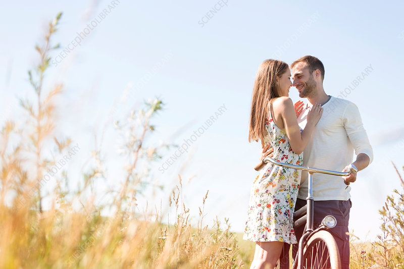 Couple with bike hugging in rural field
