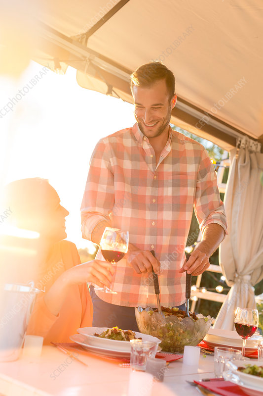 Man serving salad to wife drinking wine